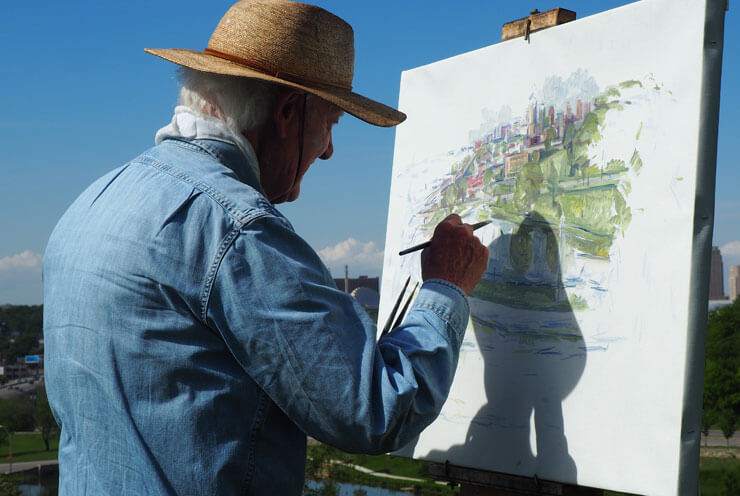 A senior is outdoors and paints a picture