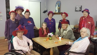 Older women in hats sit around the table