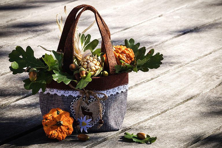 Decorative bag with pumpkins, oak leaves and acorns inside.